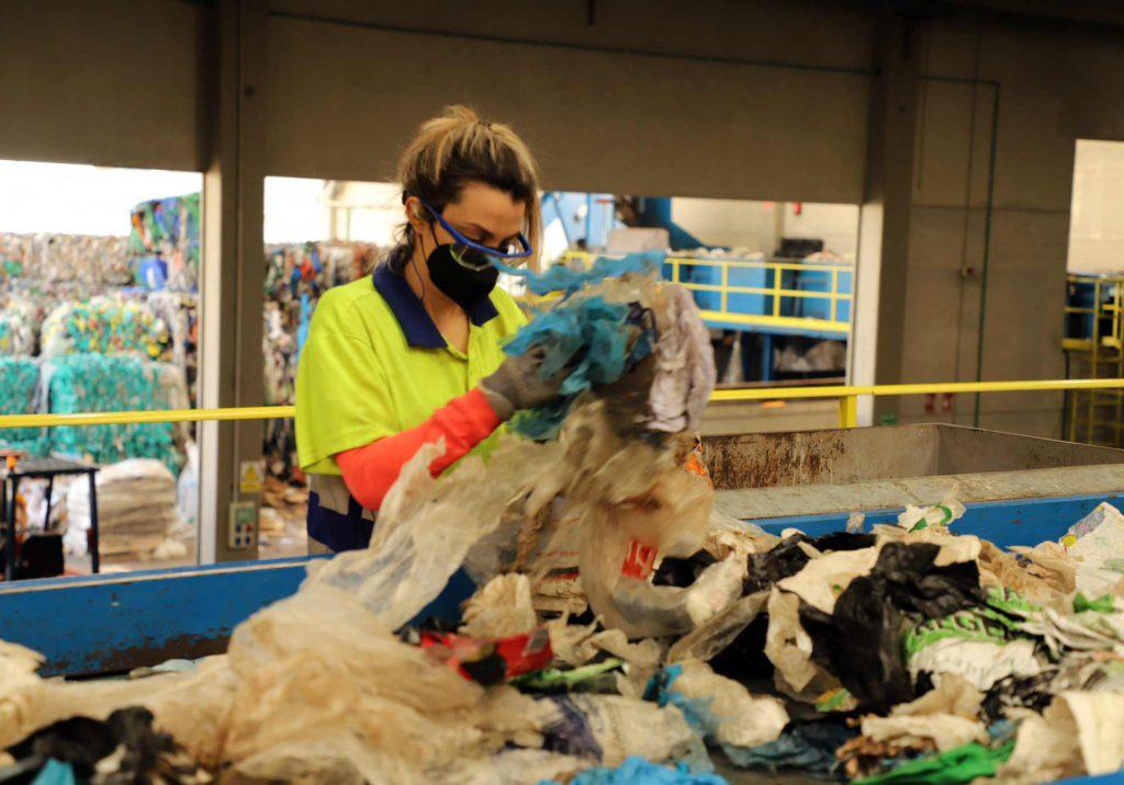 Empleada separando bolsas de basura de sus envases